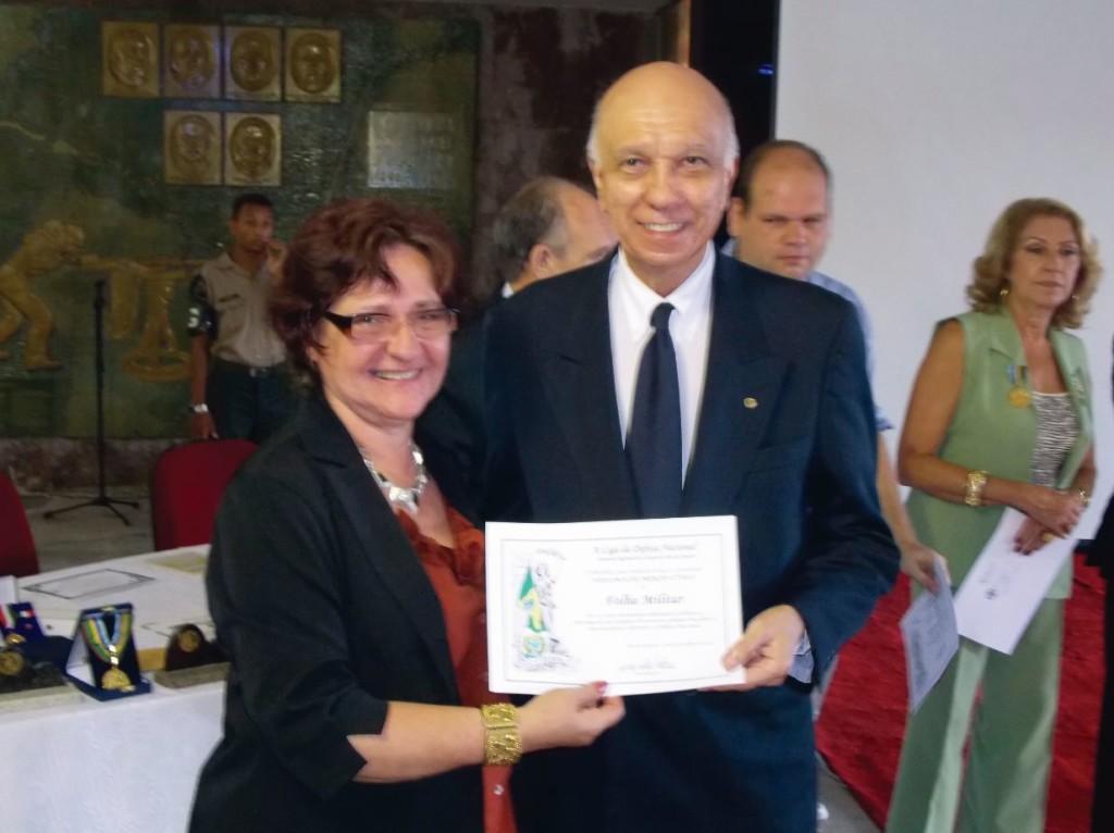 A presidente da LDN-RJ, Mirian Kátia Perolla entrega o diploma ao jornalista Luiz Carlos Pereira Coelho